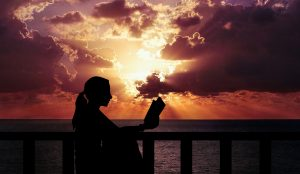 silhouette of woman reading at the ocean in front of a sunset